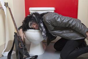 Exhausted senior male guitarist sleeping in toiletの写真素材 [FYI03644793]