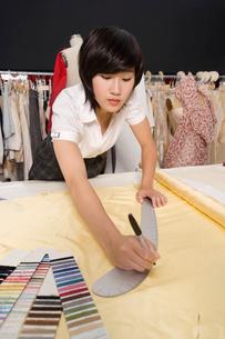 Female dressmaker measuring fabricの写真素材 [FYI03644822]