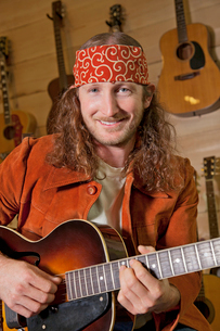 Portrait of handsome man playing guitarの写真素材 [FYI03644844]