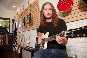 Portrait of serious mid adult man sitting in guitar storeの写真素材 [FYI03644850]