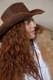 Beautiful teenager with cowboy hat and fur looking awayの写真素材 [FYI03644856]