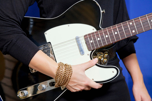 Midsection of young woman holding electric guitarの写真素材 [FYI03644865]