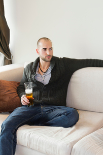 Young man sitting comfortably on sofa holding a drinkの写真素材 [FYI03644876]