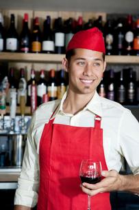 Happy handsome bartender holding glass of wine in barの写真素材 [FYI03644918]