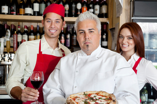 Portrait of a confident chef holding pizza with wait staff iの写真素材 [FYI03644923]