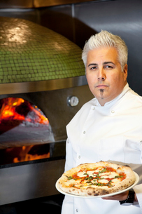 Portrait of a confident mid adult chef holding pizzaの写真素材 [FYI03644924]