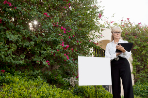 Senior real estate agent standing by sign board reading fromの写真素材 [FYI03644947]