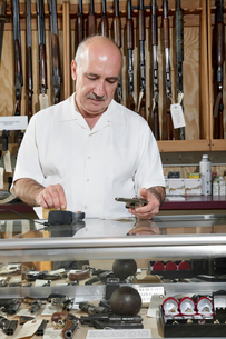 Mature male merchant at gun shop with credit card readerの写真素材 [FYI03644956]