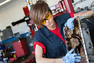 Young female mechanic working on automobile machinery part iの写真素材 [FYI03644962]