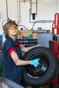 Portrait of a confident young female mechanic carrying tireの写真素材 [FYI03644964]