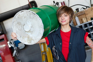 Portrait of a happy young female mechanic carrying oil drumの写真素材 [FYI03644968]