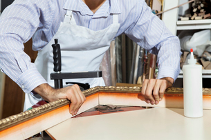 Midsection of a young craftsman working on picture frame's cの写真素材 [FYI03644986]