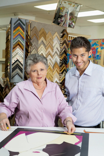Portrait of senior female owner with customer measuring pictの写真素材 [FYI03644994]