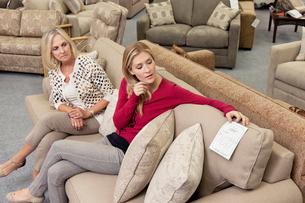 Mother and daughter sitting on sofa while looking at price tの写真素材 [FYI03644998]