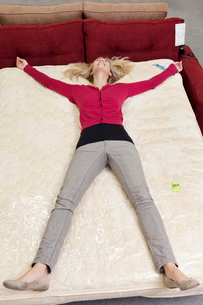 High angle view of woman lying on mattress in furniture storの写真素材 [FYI03645000]