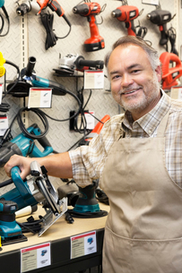 Portrait of a happy salesperson with electric saw in hardwarの写真素材 [FYI03645008]