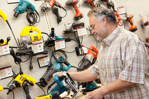 Side view of mature salesperson looking at electric sawの写真素材 [FYI03645010]