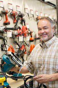 Portrait of a happy hardware store owner with electric sawの写真素材 [FYI03645011]