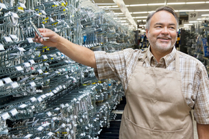 Happy mature salesperson holding metallic equipment while loの写真素材 [FYI03645016]
