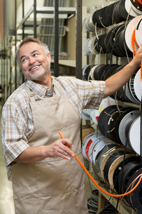 Happy mature salesperson standing by electrical wire spool wの写真素材 [FYI03645020]