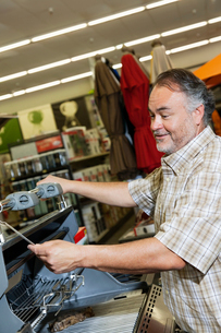 Mature man looking at price tag of machinery in hardware stoの写真素材 [FYI03645026]