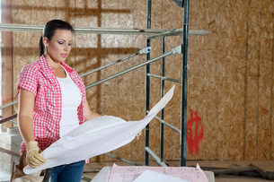 Young female contractor looking at building plans with scaffの写真素材 [FYI03645048]