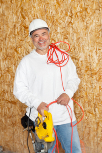 Portrait of a happy male construction worker holding a powerの写真素材 [FYI03645070]
