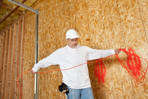 Mature male construction worker with an electrical wireの写真素材 [FYI03645071]