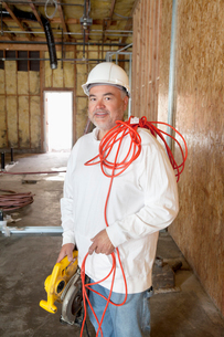 Portrait of a smiling male construction worker holding a powの写真素材 [FYI03645075]