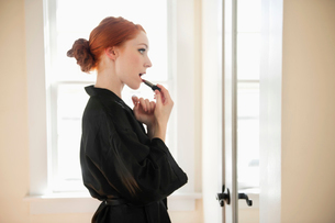 Profile view of a young woman in robe applying lipstickの写真素材 [FYI03645077]