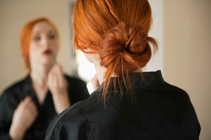 Back view of young woman applying makeupの写真素材 [FYI03645081]