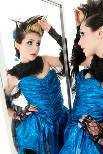 Beautiful young woman looking at herself in mirrorの写真素材 [FYI03645153]