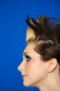 Side view of young woman with spiked hair over colored backgの写真素材 [FYI03645186]