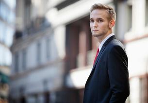 Portrait of handsome businessman in suit standing against buの写真素材 [FYI03645195]