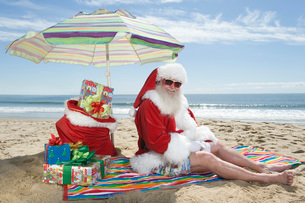 Father Christmas sits under a parasol on the beachの写真素材 [FYI03645213]