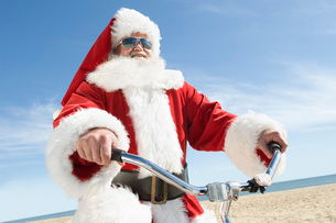 Father Christmas cycles along beach frontの写真素材 [FYI03645220]