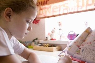 10 year old girl sits at window desk doing her homeworkの写真素材 [FYI03645267]