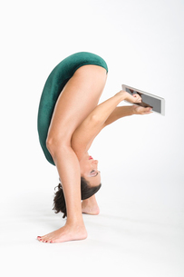 Woman  using digital tablet while exercisingの写真素材 [FYI03645328]