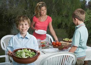Mother and sons (6-11) preparing dinner table in garden boyの写真素材 [FYI03645364]
