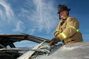 Firefighter hitting crashed car with hammerの写真素材 [FYI03645420]
