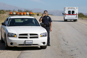 Police officer using CB radio on desert roadの写真素材 [FYI03645425]