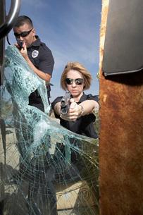 Police officers aiming guns through broken car windshieldの写真素材 [FYI03645432]