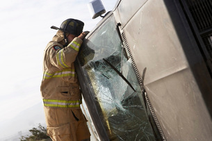 Firefighter looking into crashed carの写真素材 [FYI03645436]