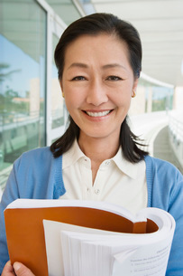 Woman embracing book at school smiling portraitの写真素材 [FYI03645496]