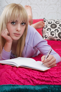 Portrait of teenager (16-17) lying on bed writing diaryの写真素材 [FYI03645518]