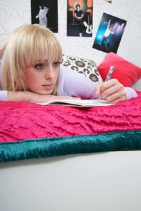 Portrait of teenager (16-17) lying on bed writing diaryの写真素材 [FYI03645520]