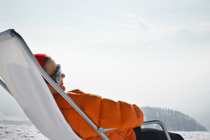 Person sitting in lawn chair in snowの写真素材 [FYI03645546]