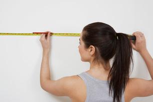 Woman measuring wallの写真素材 [FYI03645549]