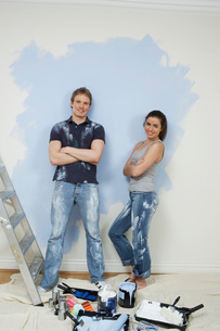 Couple resting while painting wall portraitの写真素材 [FYI03645561]