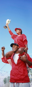 Woman holding trophy sitting on man's shoulders low angle viの写真素材 [FYI03645578]